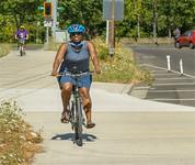 Woman bicyclist wearing a helmet on a bike path