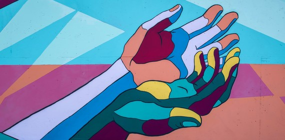 Image description: Bright, multi-color painted mural of two diferent hands coming together, with palms facing up.