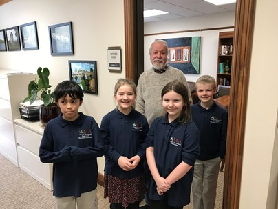 Senator Riley stands at the door of his office with 4 children in Montessori shirts