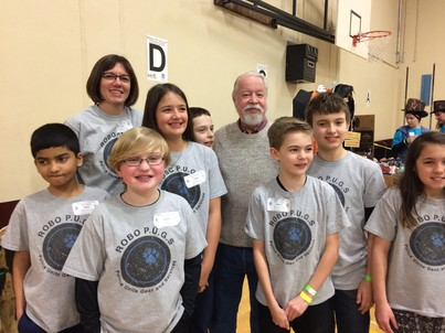 Sen. Riley stands with a group of 7 students with their teacher in a school gym