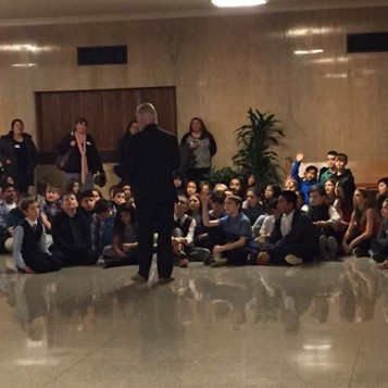 Sen. Riley's back is to the camera and he is addressing a large group of students sitting on the ground outside the Senate chamber