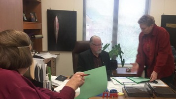 Sen. Riley sits at his desk while two women talk to him and point to materials they brought