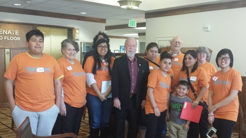 Senator Riley stands with a group of constituents all wearing orange tshirts in the 3rd floor senate wing lobby area