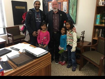 Sen. Riley stands with a gentleman and 3 young girls in his Capitol office