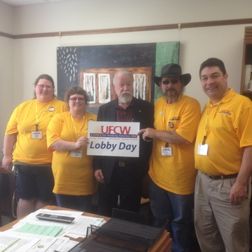 Sen. Riley standing with 4 people in bright yellow shirts