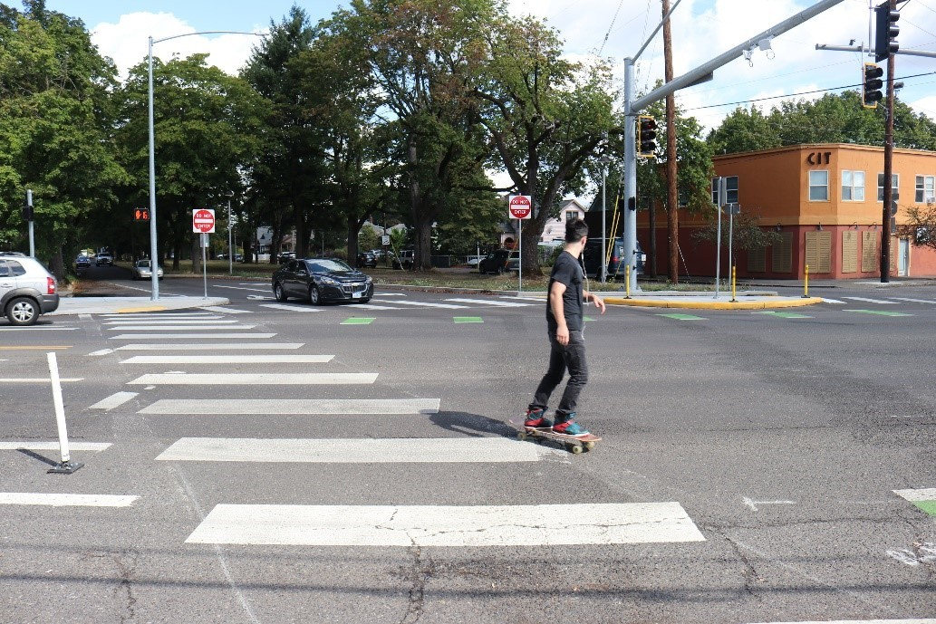 Skateboarder using a new crosswalk on Foster Road