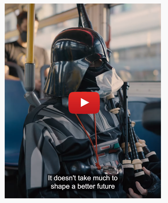 A screen shot of the Get Outside to Get Going video starring the Unipiper on a TriMet bus wearing a Darth Vader helmet and a mask