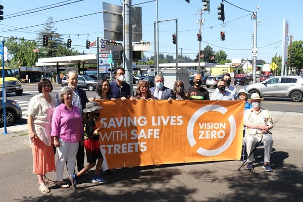 Elected officials and community leaders hold up a Vision Zero banner at the corner of 82nd Avenue and NE Glisan.