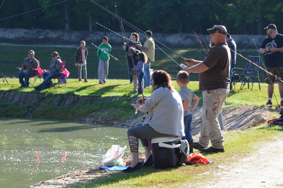 People fishing around a pond for a youth fishing rodeo.