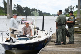 SCDNR officers talking with people in a boat from a dock.