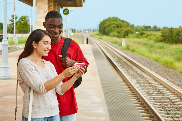 Man and woman looking at cell phone on A-train platform