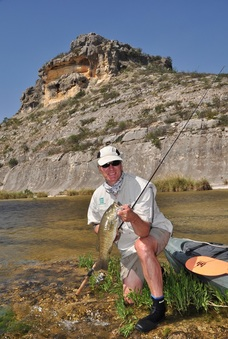 Man river fishing with kayak nearby