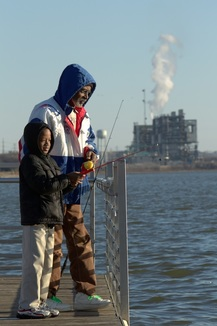 man and son fishing at a power plant lake