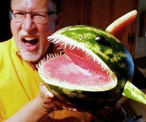 man holding a shark made from a watermelon
