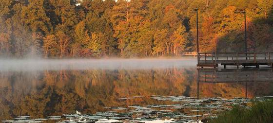 Mist on the water of a lake with a pier and autumn color