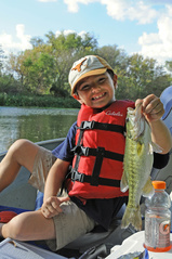 Boy holding a Guadalupe bass he caught fishing.