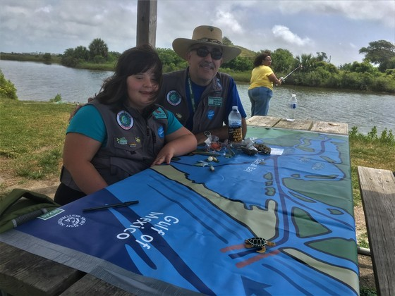 Father and daughter teaching using Habitat Mat by the water