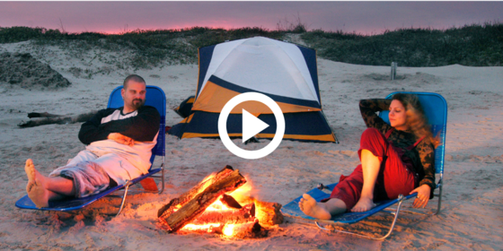 couple camping on beach with a campfire, video