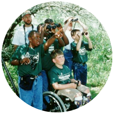 boy in wheelchair surrounded by friends