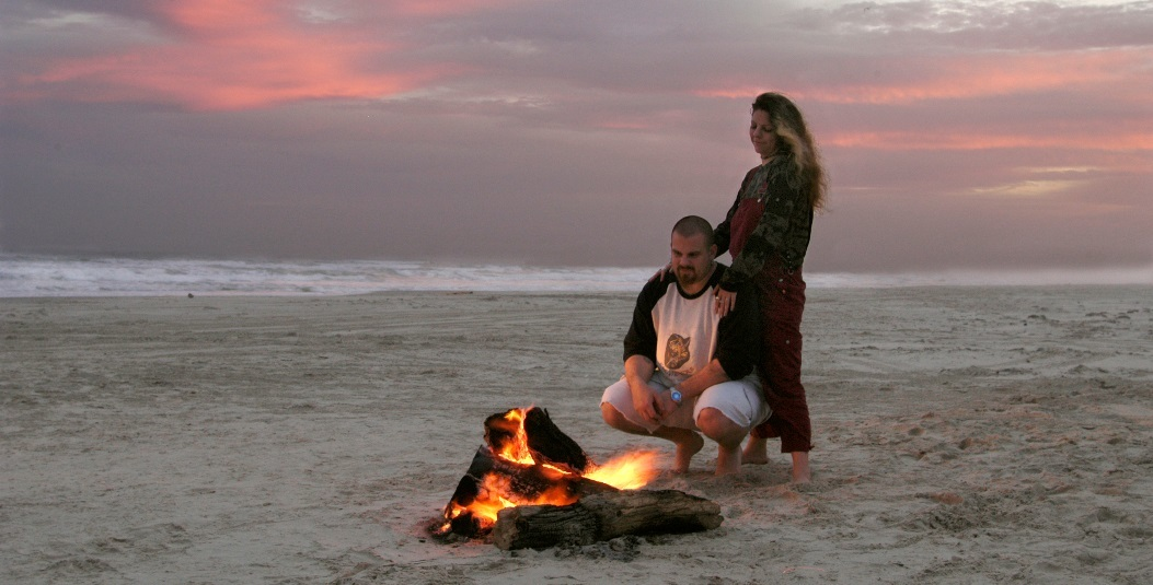 couple on beach with campfire