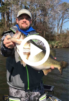 man in boat holding largemouth bass, video link