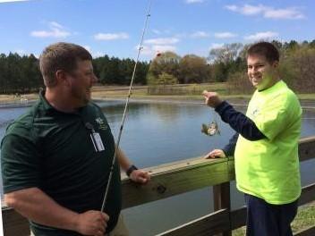 man helping participant fish