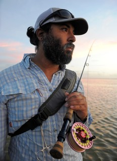 man on saltwater holding fly fishing rod