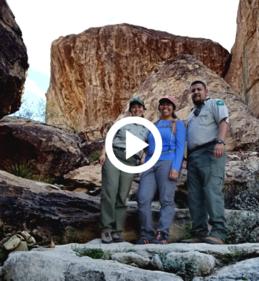 Ambassadors in front of a giant boulder