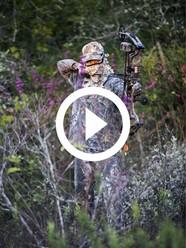 Archer in camo taking aim