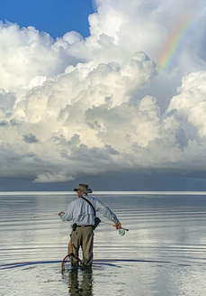 man surf fishing with rainbow in clouds