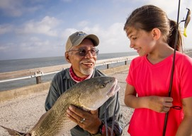 man holding redfish as child looks on
