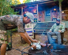 2 guys in deer camp cooking at grill