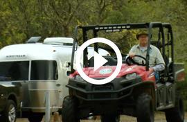 Volunteer in vehicle by Airstream, video link