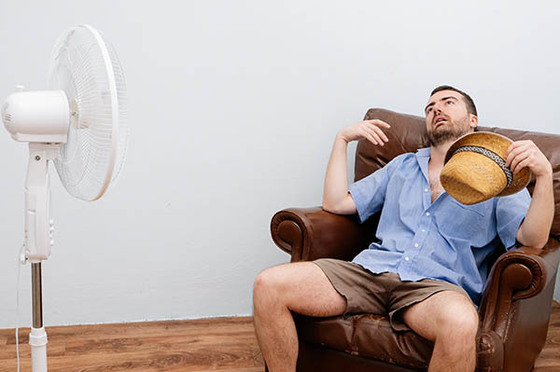 Man Sitting in Front of a Fan