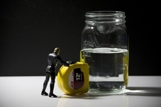 Action figure measuring glass of water