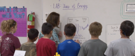 Photo of teachers and students at a whiteboard