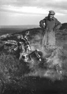 B&W photograph of a man standing by a broken down motorcycle that appears to be stuck in the mud on the moor and is steaming slightly...