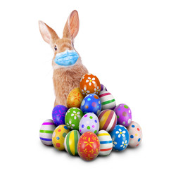 Easter bunny wearing a mask sitting on decorated eggs