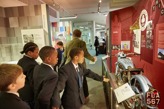 Group of students discuss a motorbike exhibit in the Brent Museum