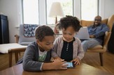 two young children playing with a tablet, with a parent in the background