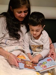 Woman and young child read in bed together