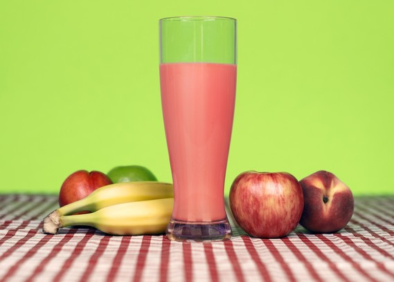 Banana apple and nectarine smoothie in a glass on a table with a tablecloth