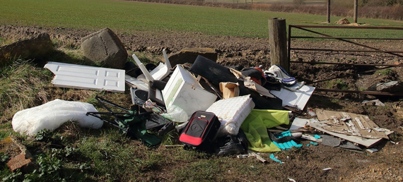 Fly tipping in a field showing an old doors, suitcase and other household items laid on the ground