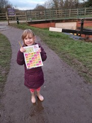 Girl holding scavenger hunt paper outside on a walk
