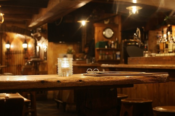 Pub setting with menu in the foreground and beer pumps and drinks blurry in the background
