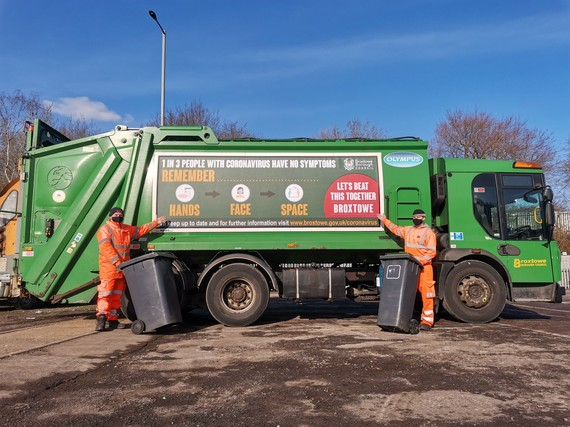 Two refuse collection people and new lorry with advertising about hands, face and space
