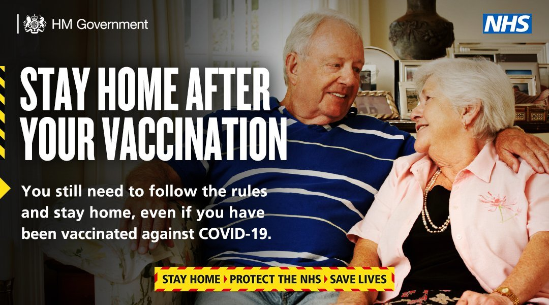 Stay at home after your vaccination image of husband and wife sat of the sofa