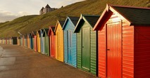 colourful beach huts by the coast in England