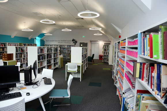 the interior of one of Derbyshire's libraries in Glossop with bookshelves and computers