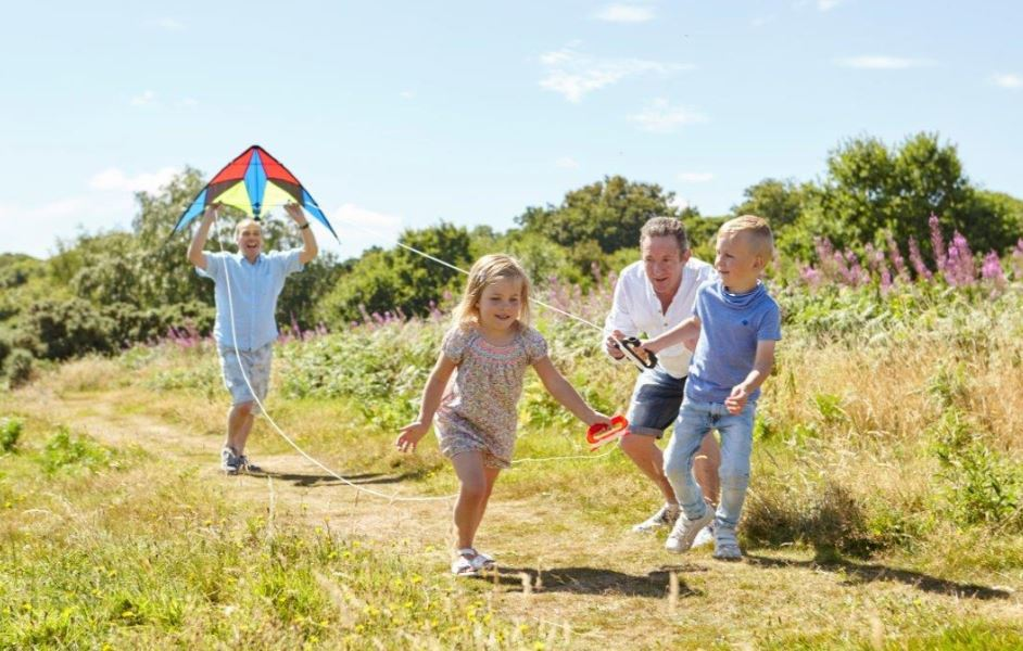 considering adoption? family with children running with a kite in the sunshine